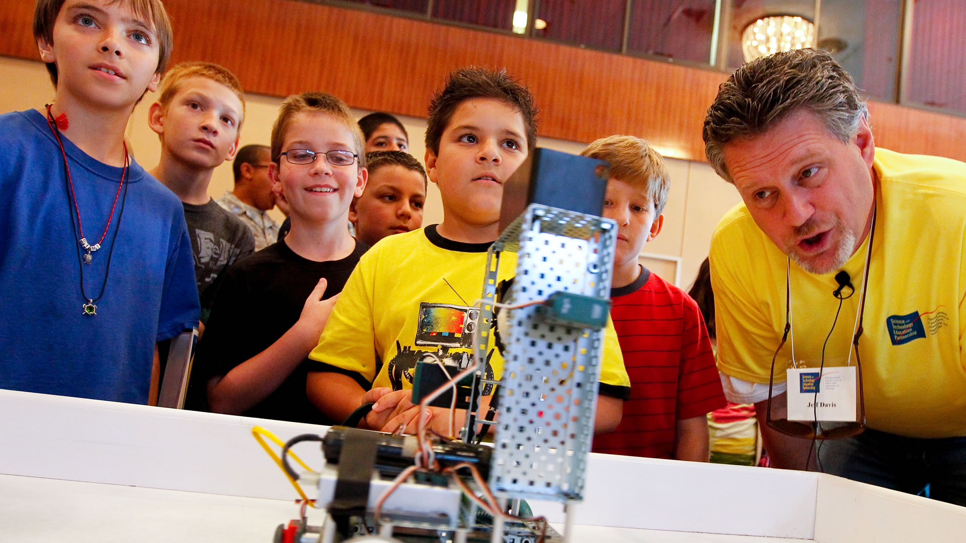 Teacher and students operating a small robot.